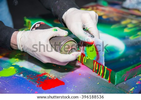 Man hands in gloves holding and drawing by graffiti spray - stock photo