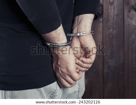 man hands in handcuffs  - stock photo