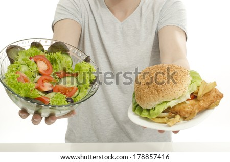 Man hands offering you a salad and a hamburger. Unrecognizable person holding in front a bowl of salad and a big burger. Choosing between good healthy food and bad unhealthy food. - stock photo