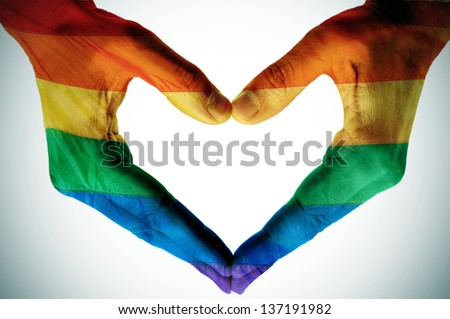 man hands painted as the rainbow flag forming a heart, symbolizing gay love - stock photo