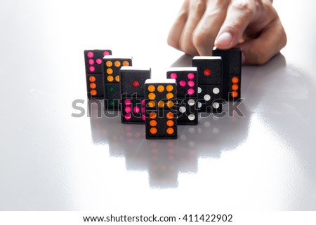 Man Hands playing domino on shiny desk (Focus on Domino and blur out hands) - stock photo