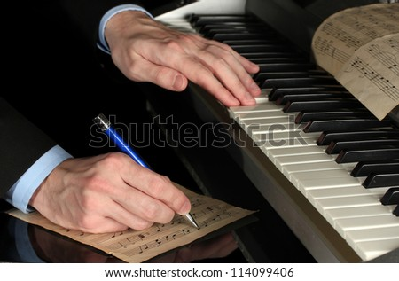 man hands playing piano and writes on parer for notes - stock photo