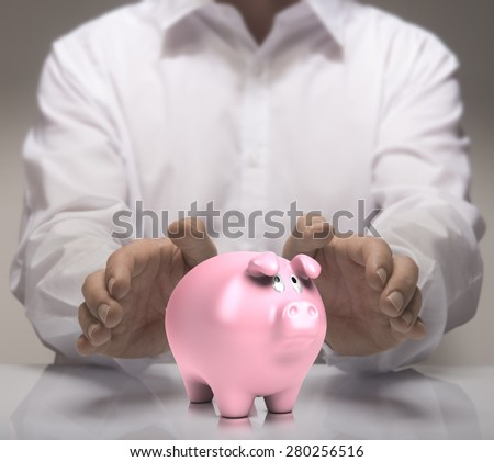 Man hands protect piggy bank. Finance concept illustration of savings or good credit.  - stock photo