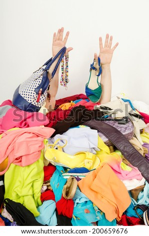 Man hands reaching out from a big pile of clothes and accessories. Man buried under an untidy cluttered woman wardrobe. Man reaching for help from to much woman shopping. - stock photo