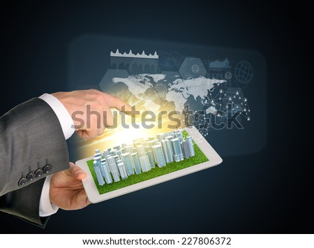 Man hands using tablet pc. Business city on touch screen. Virtual elements near computer. Business concept
