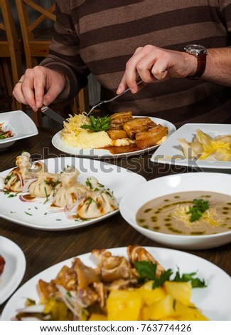 man hands with a knife and fork at a table with many different food