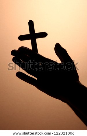 man hands with crucifix, on brown background - stock photo