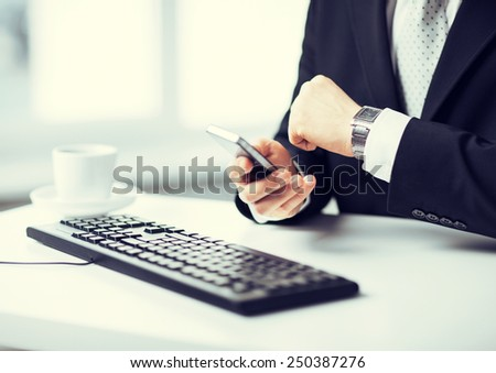 man hands with keyboard watching time and holding smartphone - stock photo