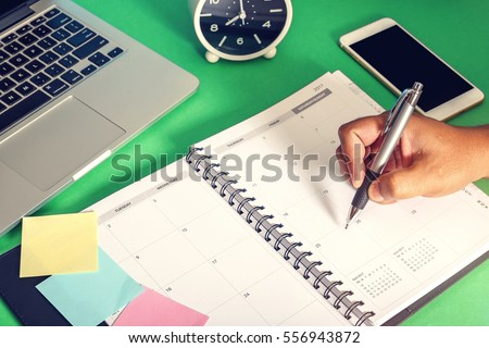 Man hands writing notes in daily planner