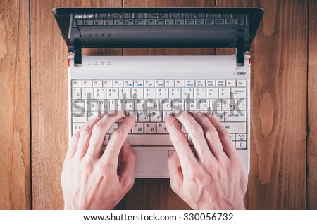 Man hands writing text on little laptop - stock photo
