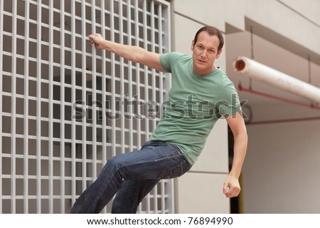 Man hanging from a building - stock photo