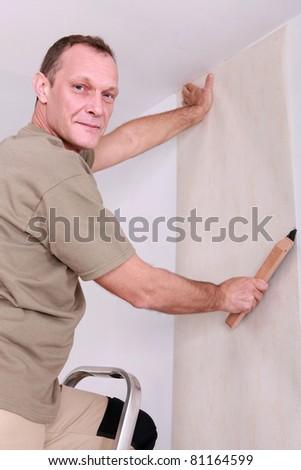 Man hanging wallpaper - stock photo