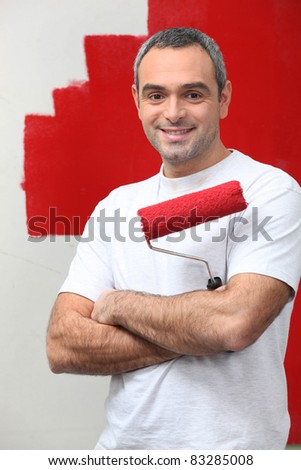 man happy to paint his wall - stock photo