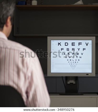 Man has eyes testing with electronic chart - stock photo