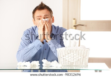 Man having a cold holding tissue with box full of tissues - stock photo
