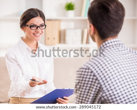 Man having a conversation with his psychotherapist on couch in office. - stock photo