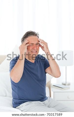 Man having a headache on his bed - stock photo