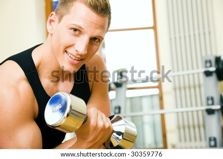 Man having a workout with dumbbell in the gym - stock photo