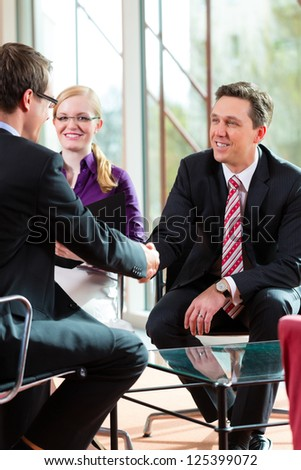 Man having an interview with manager and partner employment job candidate hiring resume CEO work business shaking hands - stock photo