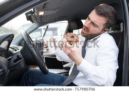 Man having breakfast and driving seated in his car