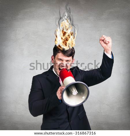man having his brain on fire because of stress on a gray background - stock photo