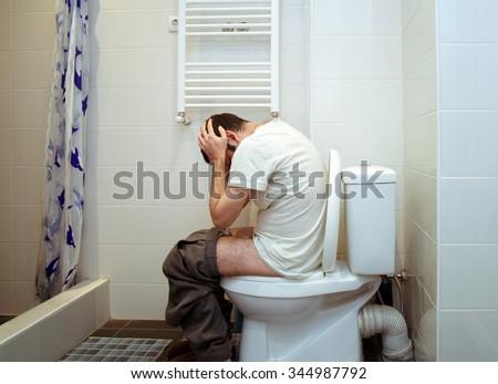 man having problems in toilet - stock photo