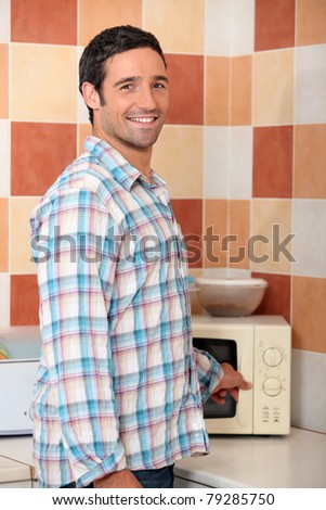 Man heating food in microwave - stock photo