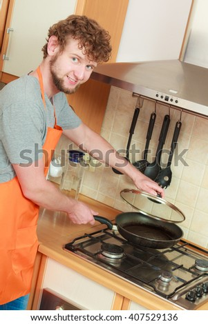 Man heating frying fry pan on burning gas burner stove in kitchen.