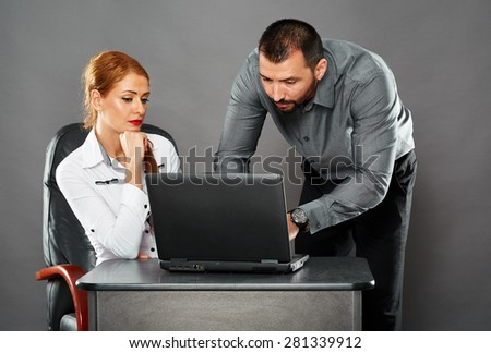 Man helping his business colleague with something on her laptop, collaboration concept - stock photo