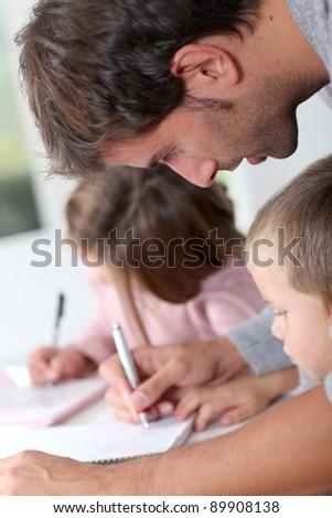 Man helping kids with homework - stock photo