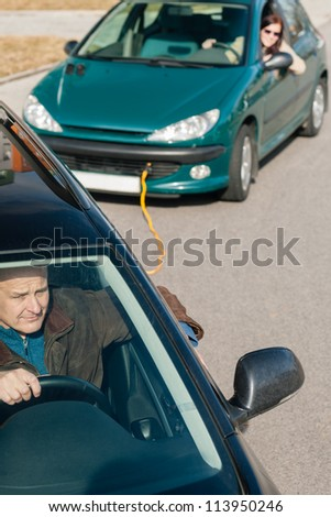 Man helping woman by pulling her car breakdown problem trouble - stock photo