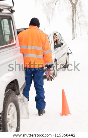 Man helping woman car breakdown assistance snow happy broken winter - stock photo