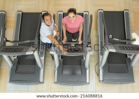 Man helping woman on treadmill in gym, elevated view