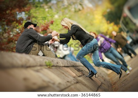 Man helping woman to climb wall in park. Shallow DOF. - stock photo