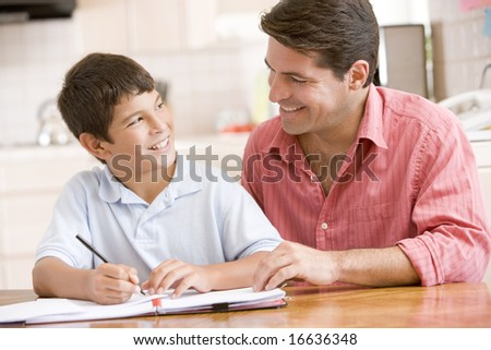 Man helping young boy in kitchen doing homework and smiling - stock photo