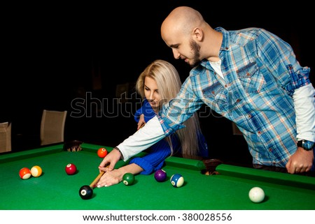 man helps a girl to play pool on the billiard table. Billiard sport concept. American pool billiard. Pool billiard game. - stock photo