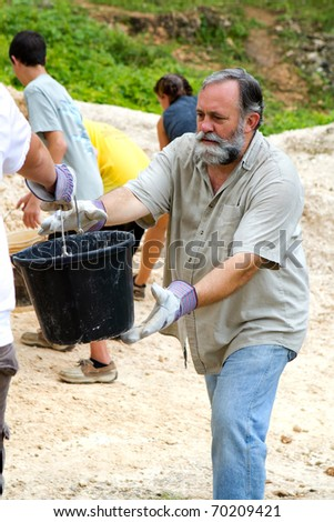 Man helps pass along a bucket of dirt to a fellow missionary on a trip to build a church in Jamaica. - stock photo