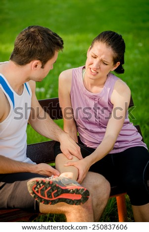 Man helps to woman who injured her leg when jogging - stock photo