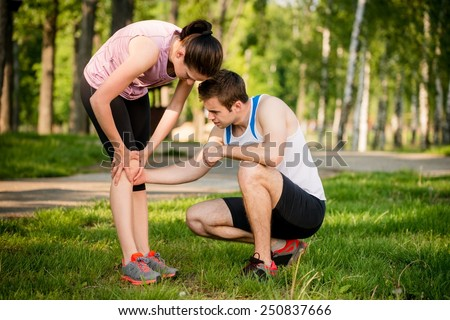 Man helps to woman with injured knee at sport activity - stock photo