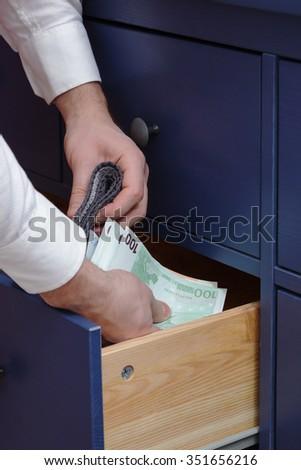 Man hides his salary in closet - stock photo