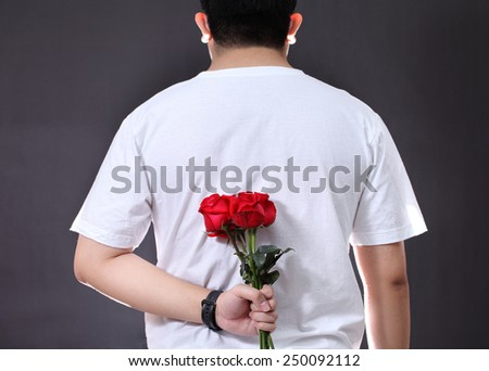 Man hiding a red rose flower behind his back.  - stock photo
