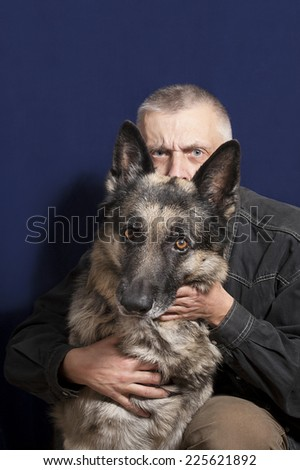 Man hiding behind a shepherd dog, safety concept, studio shot on blue - stock photo