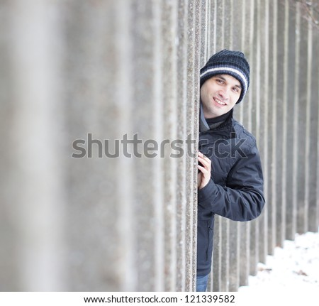 Man hiding behind stone columns on a winter day