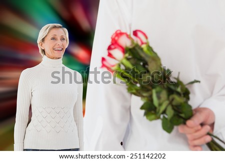 Man hiding bouquet of roses from older woman against blurred lights - stock photo