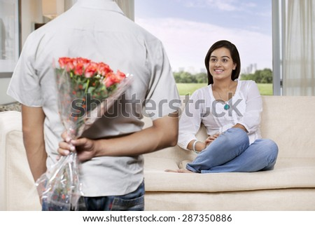 Man hiding bunch of flowers behind back while woman watching - stock photo