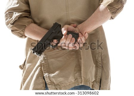 Man hiding gun behind his back - stock photo