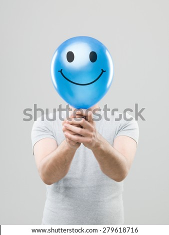 man hiding his face behing blue balloon with smiley face drawn on it, on grey background - stock photo