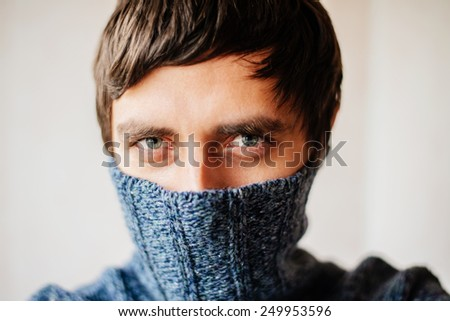 Man hiding his face in sweater. - stock photo