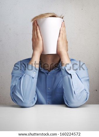 Man hiding his face with blank paper