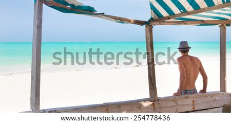 Man hiding in shade from burning tropical sun on picture perfect tropical sandy beach. Summer leisure. Shot from back.